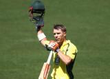David Warner de Australia celebra tras alcanzar 10...